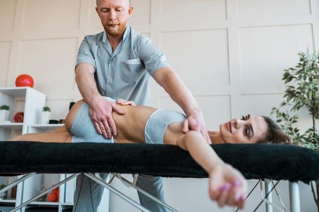 Physiotherapeut, der körperliche übungen an frau durchführt