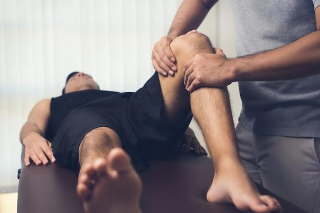 Physiotherapeut, der männlichen patienten des athleten behandelt