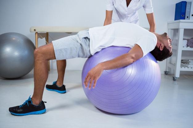 Physiotherapeut, der mann mit übungsball unterstützt