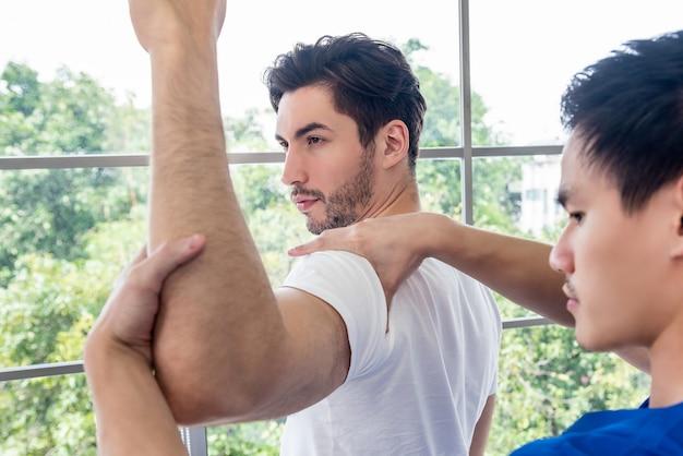 Physiotherapeut, der masssage gibt und männlichen geduldigen schulter und arm des athleten ausdehnt