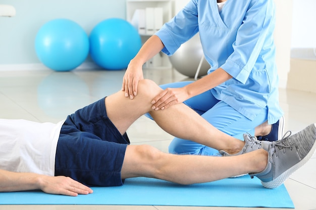 Physiotherapeut, der mit männlichen patienten im rehabilitationszentrum arbeitet