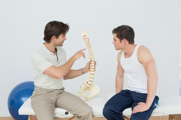 Physiotherapeut, der patienten etwas auf skeleton modell zeigt