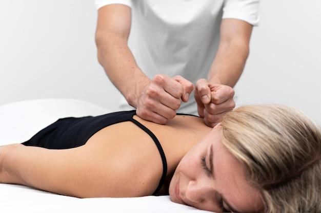 Physiotherapeut, der rückenmassage auf frau durchführt
