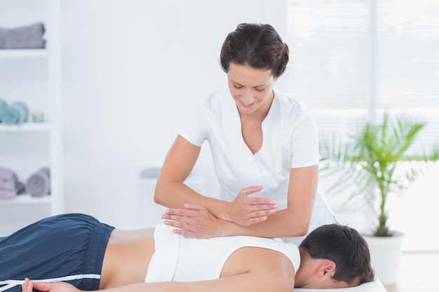 Physiotherapeut, der rückenmassage tut