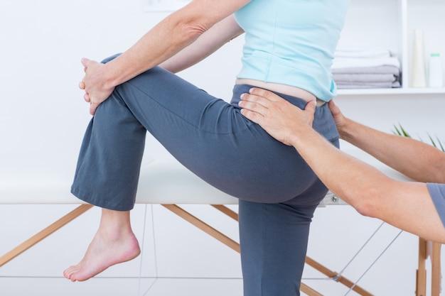 Physiotherapeut, der seine patientenrückseite überprüft