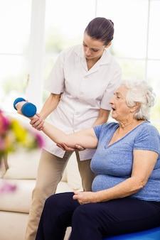 Physiotherapeut, der sich zu hause um krankem älterem patienten kümmert