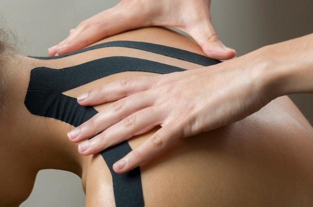 Physiotherapeut, der sich zurück auf schwarzes kinesio band auf frauenpatienten setzt