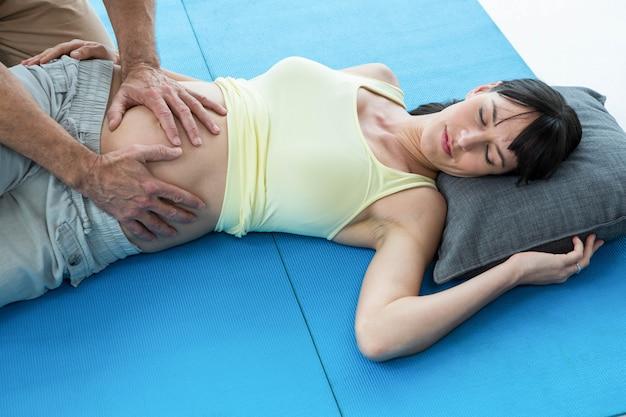 Physiotherapeut, der zu hause bauchmassage schwangere frau antut