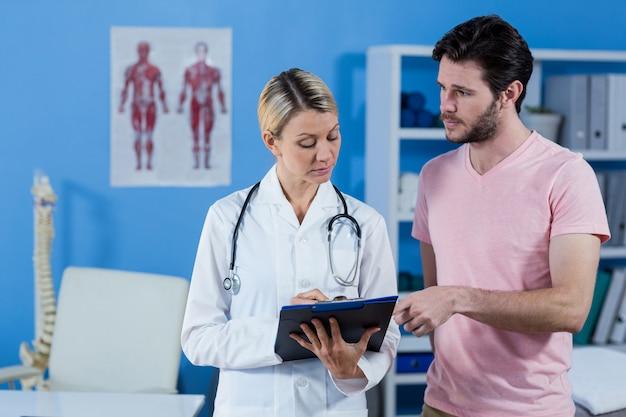 Physiotherapeut erklärt dem männlichen patienten die diagnose