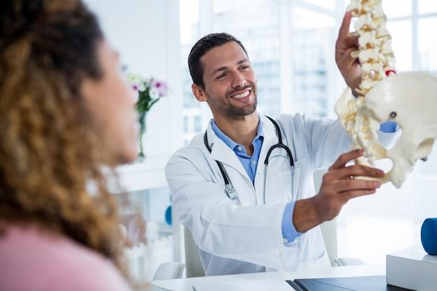Physiotherapeut erklärt dem patienten das wirbelsäulenmodell