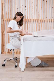 Physiotherapeut frau, die dem weiblichen patienten in der klinik eine fußmassage gibt