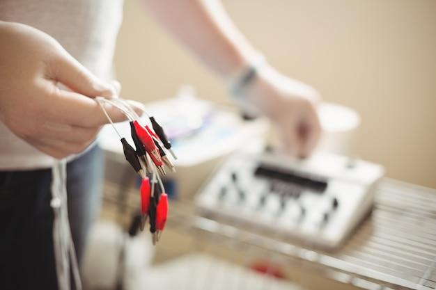 Physiotherapeut hält das kabel der elektrotrockennadeleinheit