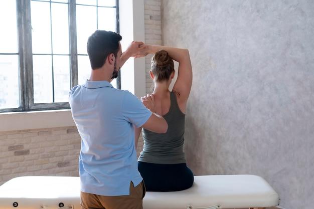 Physiotherapeut hilft dem patienten, den mittleren schuss zu dehnen