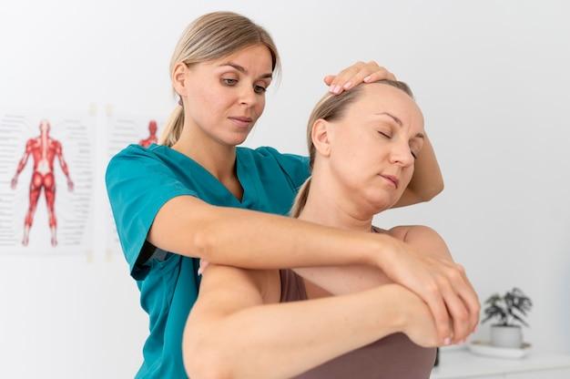 Physiotherapeut hilft einem patienten in ihrer klinik