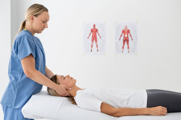 Physiotherapeut hilft einer jungen patientin