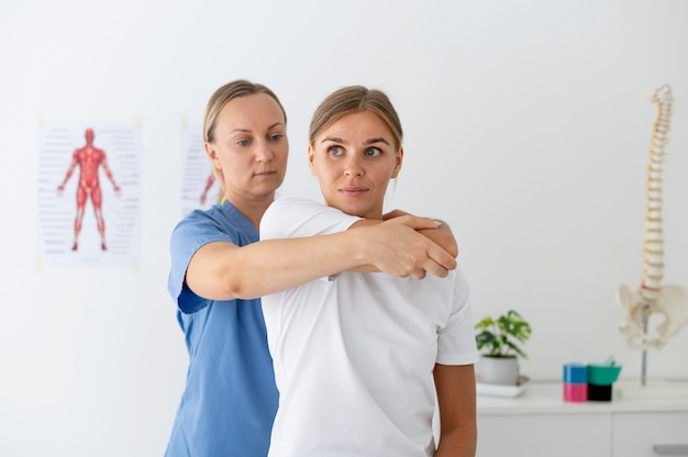 Physiotherapeut hilft einer patientin in ihrer klinik