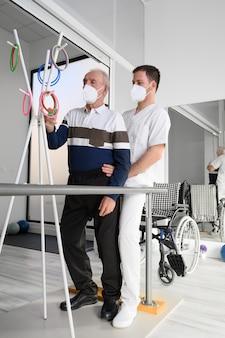Physiotherapeut hilft schlaganfallopfer im reha-zentrum