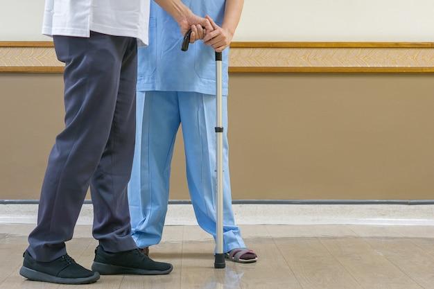 Physiotherapeut in der blauen kleidung, zum sich um die älteren personen in der klinik zu kümmern.