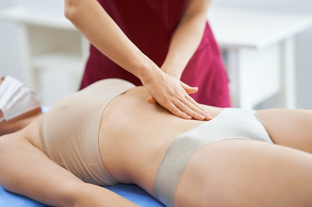 Physiotherapeut in maske hilft patientin