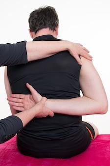 Physiotherapeut macht rückenmassage in der arztpraxis
