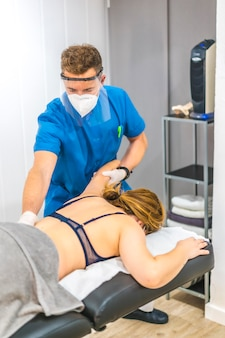 Physiotherapeut mit bildschirm und maske, die den arm eines patienten strecken. wiedereröffnung mit physiotherapeutischen sicherheitsmaßnahmen bei der covid-19-pandemie. osteopathie, therapeutische chiromassage