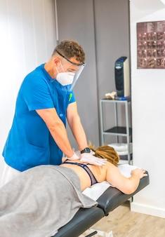Physiotherapeut mit bildschirm und maske, die den rücken eines patienten zusammendrücken. wiedereröffnung mit physiotherapeutischen sicherheitsmaßnahmen bei der covid-19-pandemie. osteopathie, therapeutische chiromassage