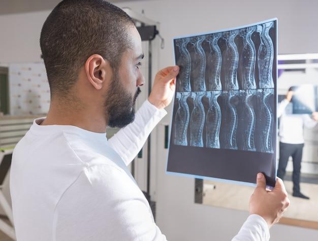Physiotherapeut mit blick auf den röntgenfilm der wirbelsäule