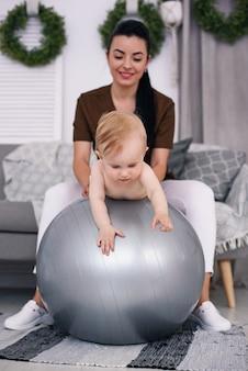 Physiotherapeut mit glücklichem baby, das übungen mit gymnastikball am medizinischen raum tut. gesundheitswesen und medizinisches konzept.