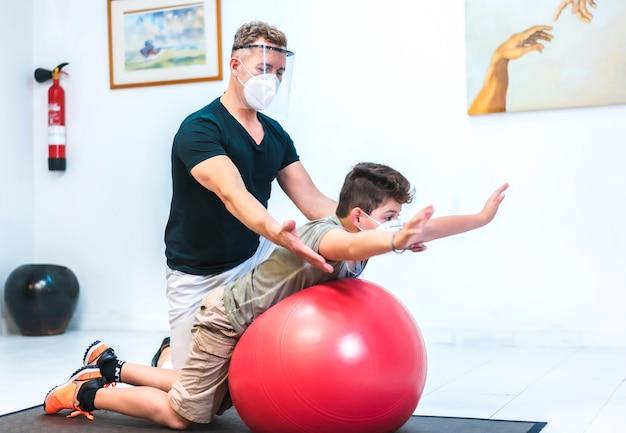 Physiotherapeut mit maske und bildschirm, der ein kind auf einem ball streckt. sicherheitsmaßnahmen von physiotherapeuten bei der covid-19-pandemie. osteopathie, therapeutische chiromassage