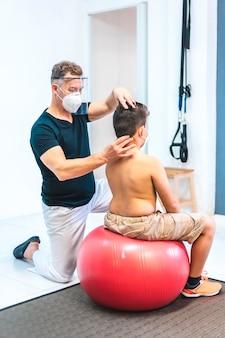 Physiotherapeut mit maske und bildschirm, die den hals eines kindes betrachten. wiedereröffnung mit sicherheitsmaßnahmen von physiotherapeuten bei der covid-19-pandemie. osteopathie, therapeutische chiromassage