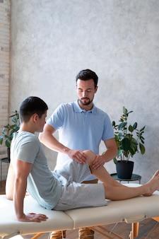 Physiotherapeut mit mittlerem schuss, der das bein überprüft