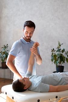 Physiotherapeut mit mittlerem schuss, der den arm überprüft