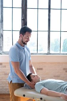 Physiotherapeut mit mittlerem schuss, der den hals massiert