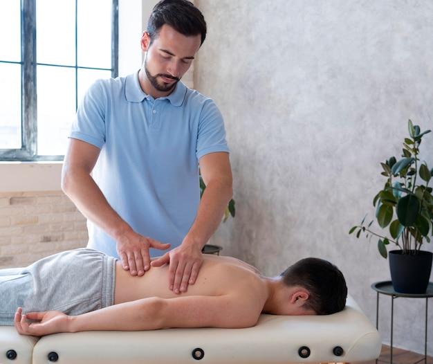 Physiotherapeut mit mittlerem schuss, der den rücken massiert