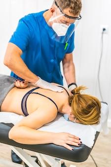 Physiotherapeut mit schutzmaßnahmen bei der arbeit mit einem patienten. covid19 pandemie. osteopathie, therapeutische chiromassage