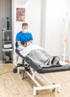 Physiotherapeut mit schutzmaßnahmen, die mit einem patienten auf der trage arbeiten, kraniale osteopathie. covid19 pandemie. osteopathie, therapeutische chiromassage