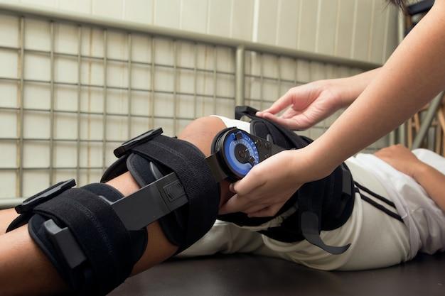 Physiotherapeut streckt übungen am bein des patienten, rehabilitation für knieverletzung