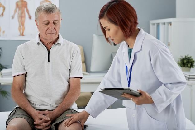 Physiotherapeut untersucht knie des patienten