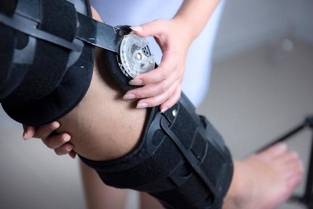 Physiotherapeuten passen die kniestütze an die des patienten an