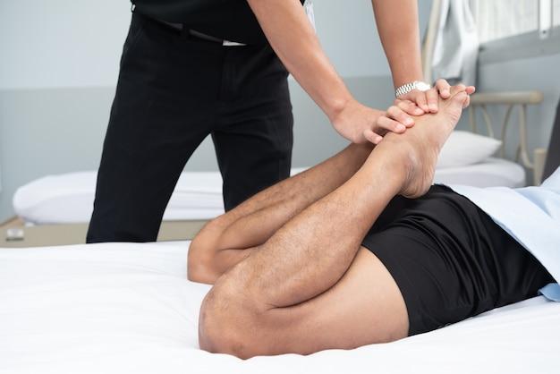 Physiotherapeuten verwenden die griffe im bein des patienten, um auf dem bett in einem medizinischen raum zu liegen.