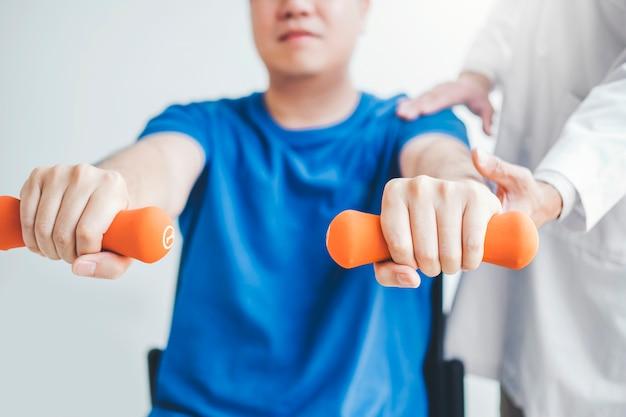 Physiotherapeutenmann, der übung mit dummkopfbehandlung über arm und schulter des physiotherapiekonzeptes des männlichen patienten des athleten gibt