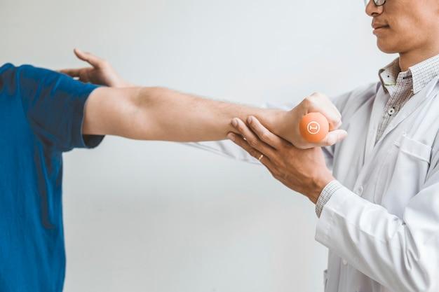 Physiotherapeutenmann, der übung mit dummkopfbehandlung über arm und schulter gibt