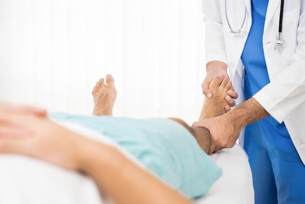Physiotherapeutentrainings-rehabilitationsübung zum patienten mit gebrochenem bein