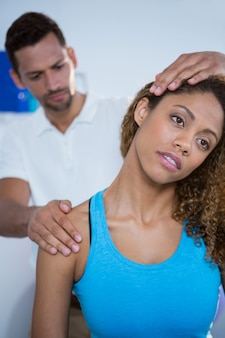 Physiotherapeutin, die der patientin eine nackenmassage gibt