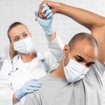 Physiotherapeutin, die die mobilität des mannes überprüft