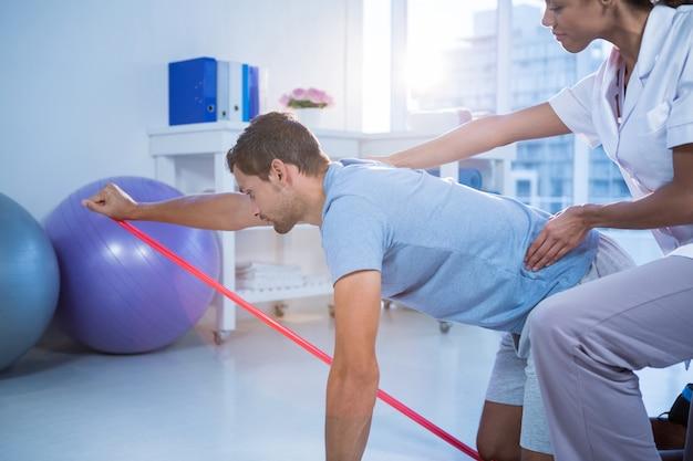 Physiotherapeutin, die einen männlichen patienten beim training unterstützt