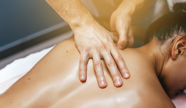 Physiotherapeutin, die einer frau in der klinik massage gibt