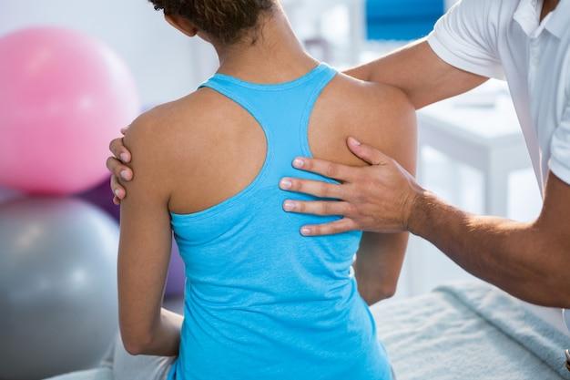 Physiotherapeutin, die einer patientin eine rückenmassage gibt