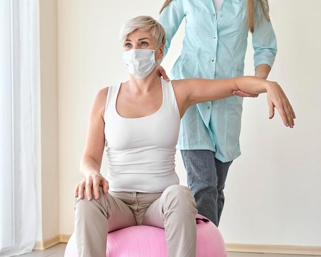 Physiotherapeutin, die sich einer therapie mit einer patientin unterzieht