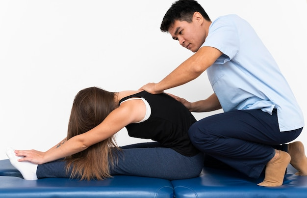 Physiotherapeutin massiert den oberen rücken der frau gegen schmerzen